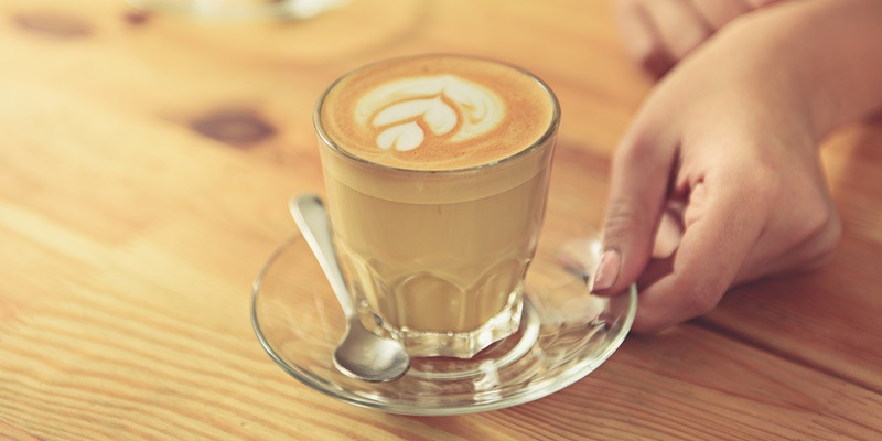 close up of female hands holding cup of delicious latte with tulip art on wooden worktop. Woman standing at bar counter in cafe