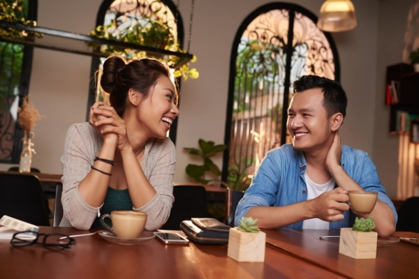Portrait of smiling Asian couple talking and flirting on date in cafe